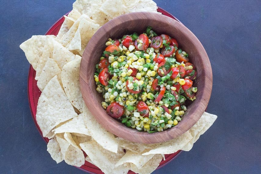 overhead of grilled corn salsa in wooden bowl on red plate with side of corn chips