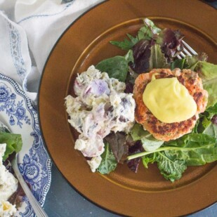 overhead of salmon burgers with aioli on a bed of greens and potato salad