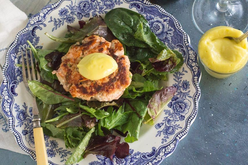 salmon burger on bed of greens with aioli and antique fork