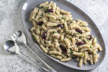 Low FODMAP Pantry Pasta with Tuna, Lemon & Olives on a gray platter with serving spoons