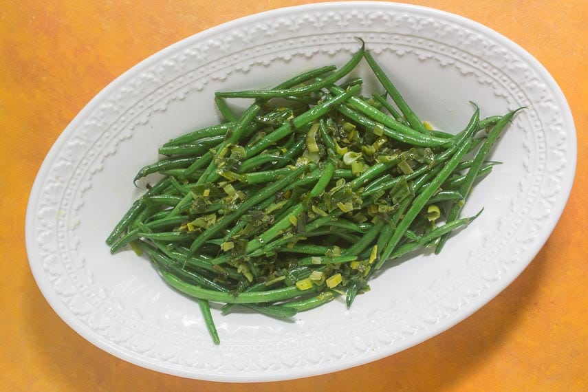 "Low FODMAP Triple ""Onion"" Green Beans on a white bowl against a deep yellow background"