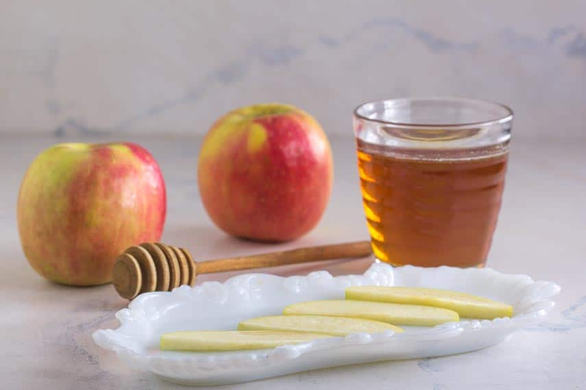apples and honey against a white backdrop