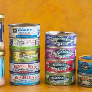 assorted cans and glass jars of tuna against a dark yellow background