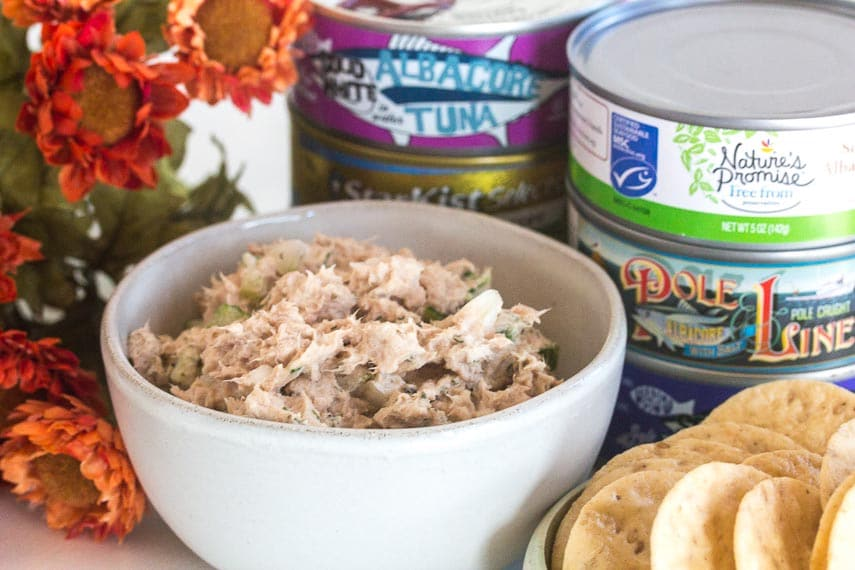 classic low FODMAP tuna salad in a small white bowl with cans of tuna in background