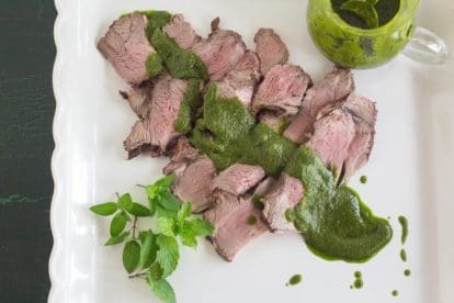 overhead image of Grilled Butterflied Leg of Lamb with Mint Salsa Verde on square white platter