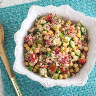 overhead image of Low FODMAP Mediterranean Tuna Salad with Chickpeas on aqua placemat with wooden spoon alongside