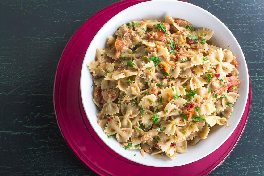 overhead image of Low FODMAP Pasta with Tuna & Sun Dried Tomatoes in white bowl on red plate