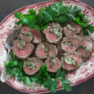 Beef Tenderloin Stuffed with Goat Cheese, Spinach & Sun-Dried Tomatoes on red and white platter with fresh parsley