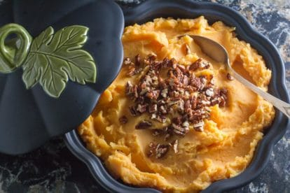 Low FODMAP Mashed Sweet Potatoes with Candied Spiced Pecans in a dark casserole dish