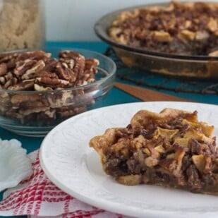 Low FODMAP Salted Caramel Apple Pecan Pie on a white plate with ingredients