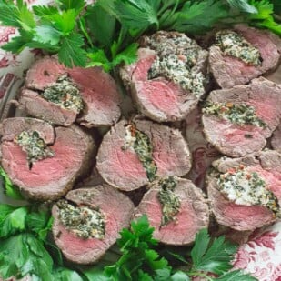 Overhead image of Beef Tenderloin Stuffed with Goat Cheese, Spinach & Sun-Dried Tomatoes on a red and white platter