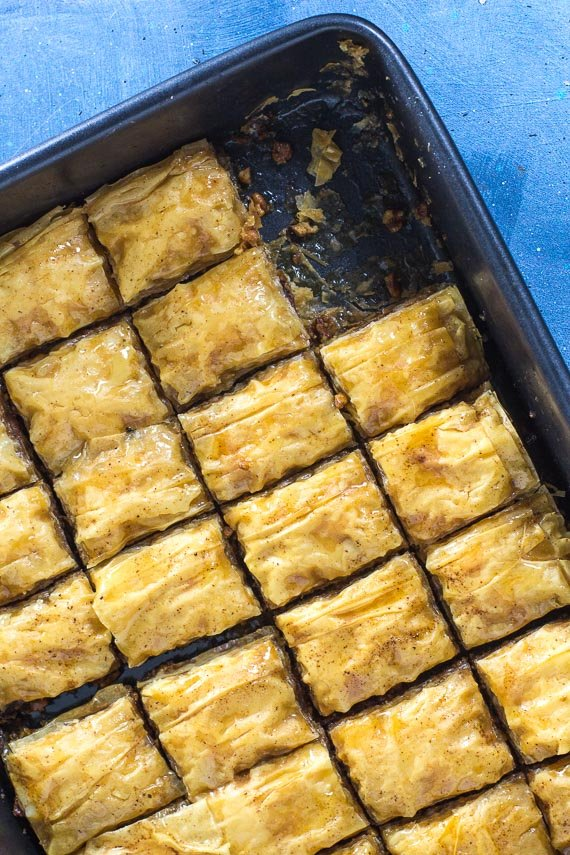 overhead image of low FODMAP walnut baklava in baking pan against blue background