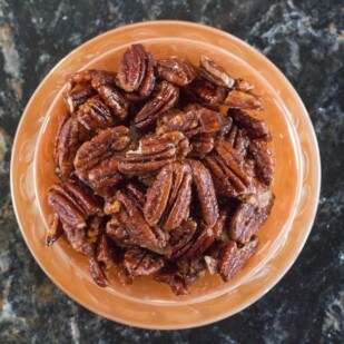 overhead of Low FODMAP Candied Spiced Pecans in orange colored dish