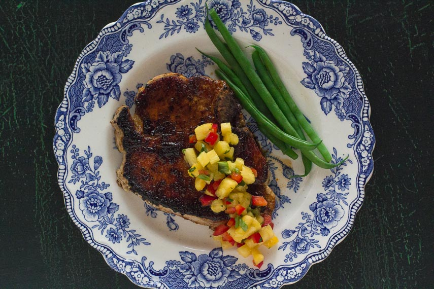 pork chop with low FODMAP Sweet & Spicy Dry Rub and Pineapple Salsa with green beans on a blue and white plate