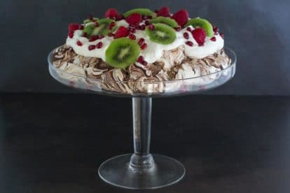 side view of Low FODMAP Chocolate Pavlova with Pomegranate, Raspberries & Kiwi in a glass pedestal dish