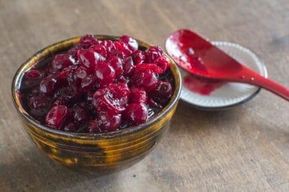 Low FODMAP Brown Sugar 5-Spice Cranberry Sauce in a dark ceramic bowl