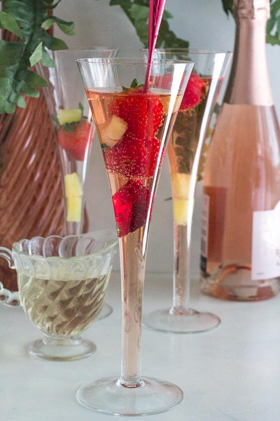 Low FODMAP Pineapple Strawberry Prosecco in champagen glass with red stirrer and pitcher of Simple Syrup