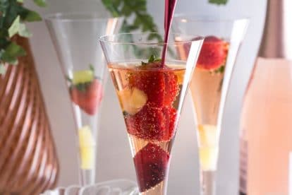 Low FODMAP Pineapple Strawberry Prosecco in champagne glass with red stirrer