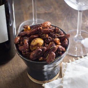 Easy Low FODMAP sweet & spicy nuts in a dark ceramic dish