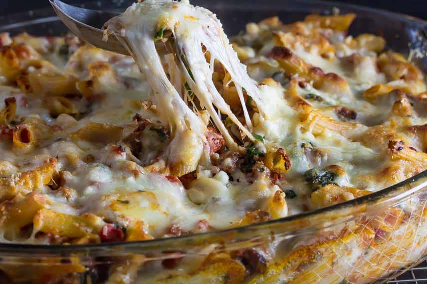 Cheesy baked ziti in glass casserole dish; fork digging in