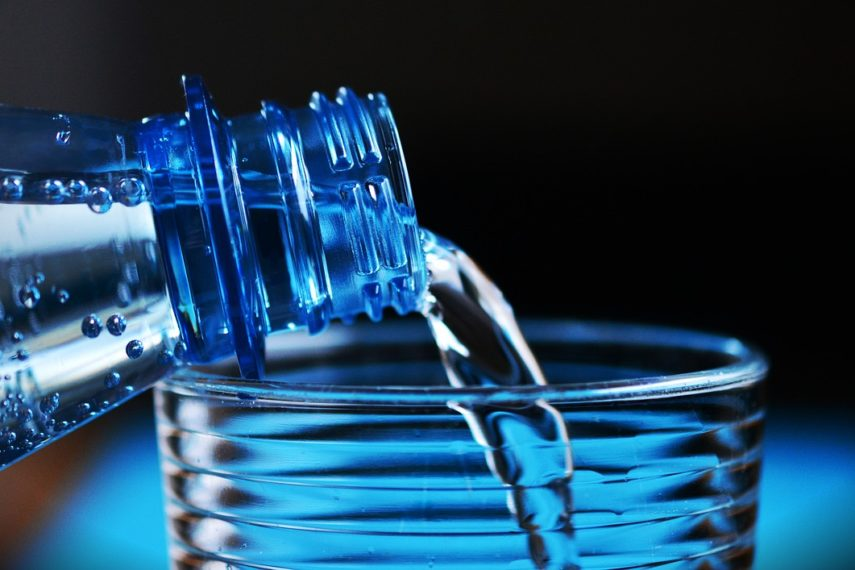 Water pouring from a bottle into a glass. - What conventional wisdom gets wrong about bloating.