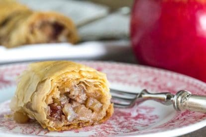 closeup of low FODMAP apple strudel on a pink and white plate with a silver fork