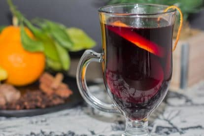 closeup of low fodmap mulled wine with orange zest on rim of clear glass mug