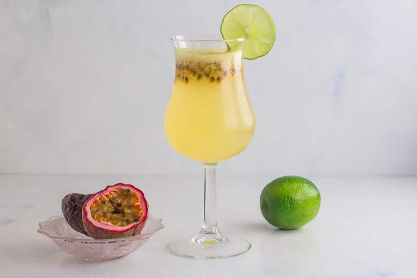horizontal image of passion for coconut drink with a lime and passion fruit in background