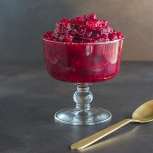 Low FODMAP horseradish cranberry sauce with gold spoon in glasss footed dish