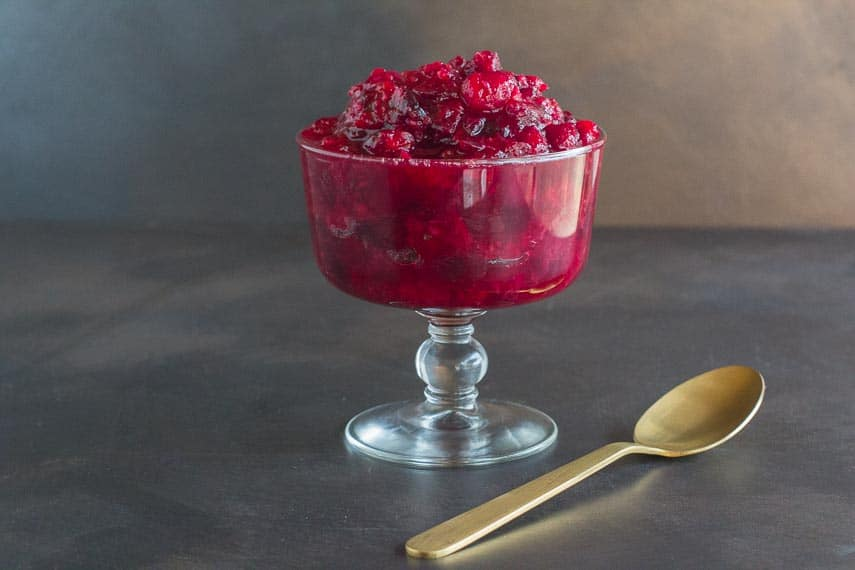 horseradish cranberry sauce with gold spoon in glasss footed dish