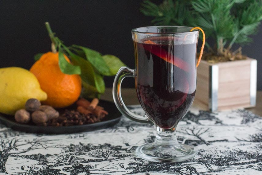 image of low fodmap mulled wine with orange zest on rim of clear glass mug