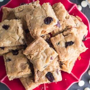 low FODMAP Cranberry white chocolate blondies on red plate overhead image