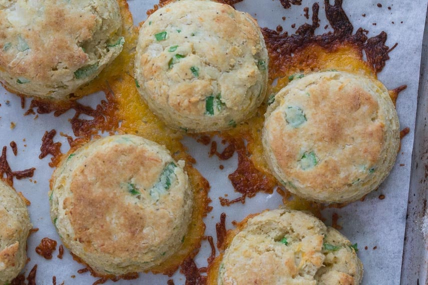low fodmap cheddar scallion biscuits on baking sheet with parchment paper and melted cheese