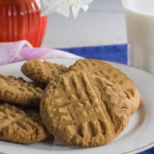 one bowl peanut butter cookies on a white plate with glass of lactose-free milk