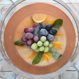 overhead image of Low FODMAP Fruited Lemonade Rosé Punch with punch cups and ladle
