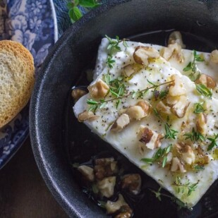 overhead image of baked feta with honey and walnuts and thyme in a cast-iron pan