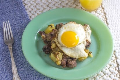 overhead of roast beef hash with fried egg and blue napkin