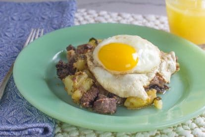 roast beef hash on green plate with fried egg on top