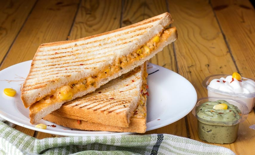 Grilled cheese sandwich sliced in half diagonally, laying on a white plate with dipping sauces off to the right