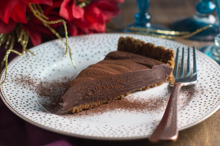 slice of Low FODMAP Cinnamon Pecan Truffle Ganache Tart on a white plate
