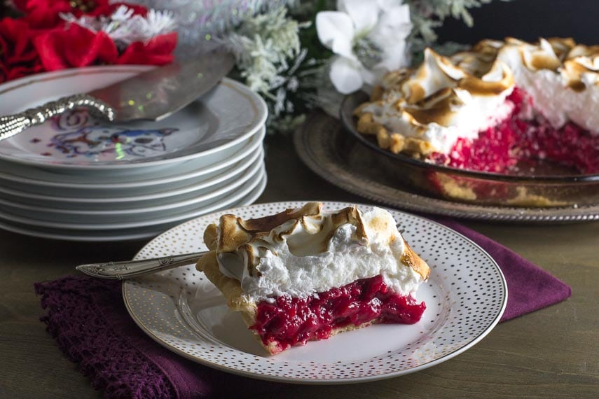 slice of cranberry snowdrift pie on a decorative plate; whole pie in background