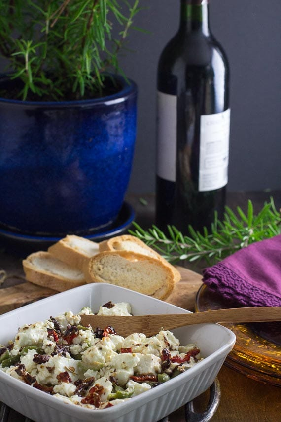 vertical image of low FODMAP baked feta with olives and sundried tomatoes with wine in background