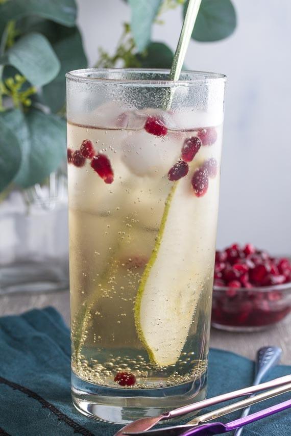 vertical image of low FODMAP ginger pomegranate pear sparkler with stirrer