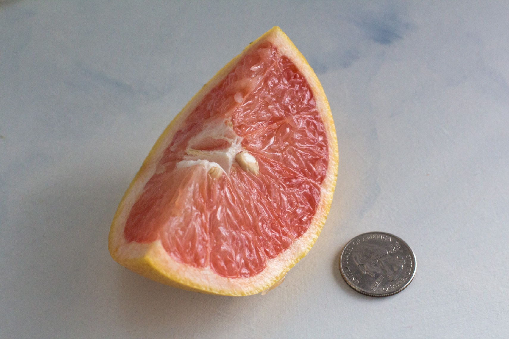 80 grams of grapefruit is low FODMAP. Here is an 80 g wedge next to a quarter for perspective