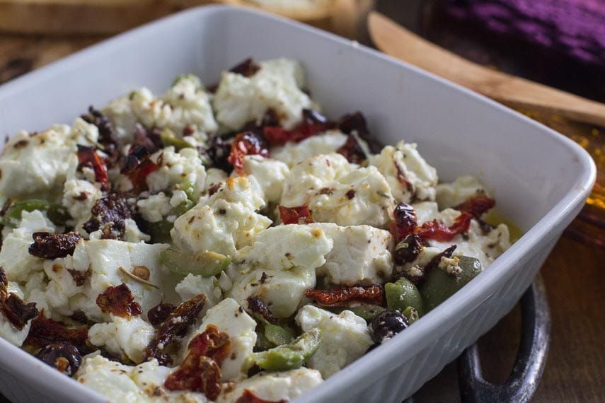 Closeup of baked feta with olives and sundried tomatoes in a white dish