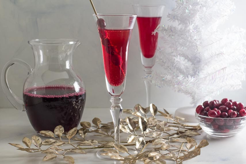 Low FODMAP Cranberry Cinnamon Swizzle in a champagne glass; cranberry juice in pitcher