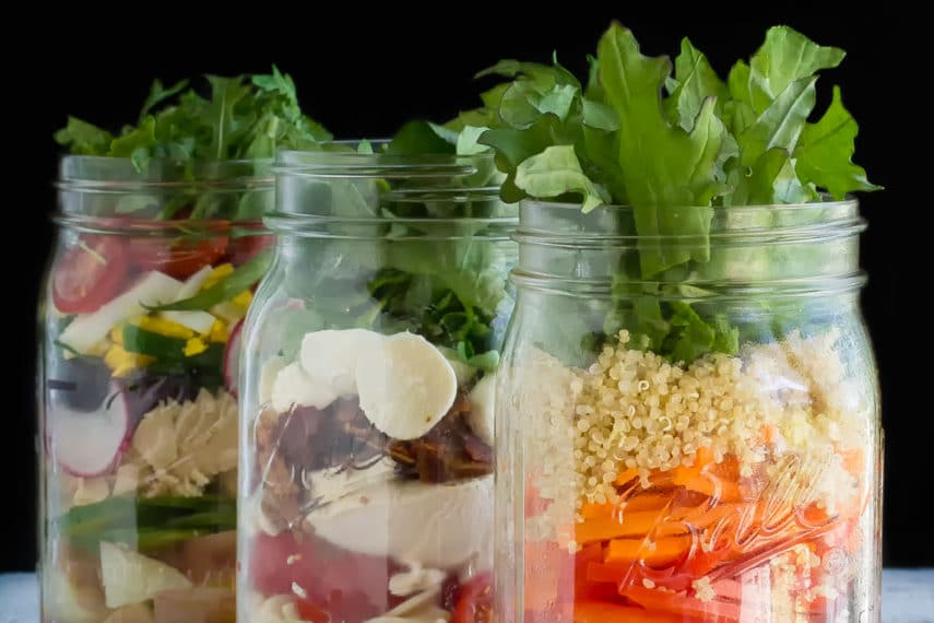 Low FODMAP Mason jar Salads in jars, vertical image, against black background