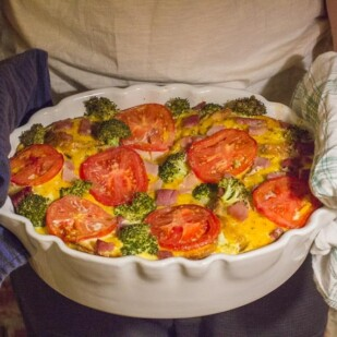 forrester holding savory bread pudding in white oval casserole