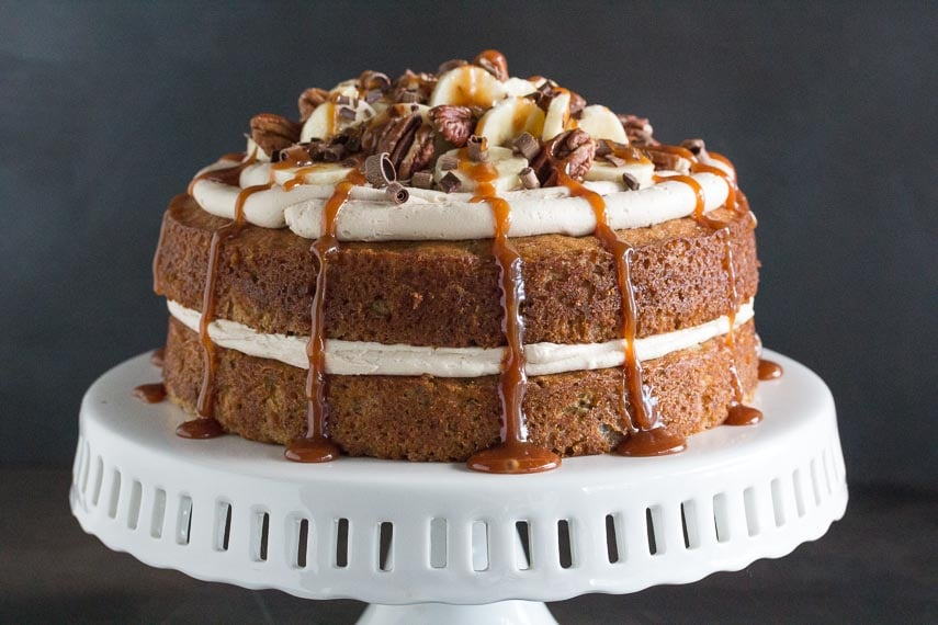 main image of low FODMAP Salted Caramel Banana Cake on a white ceramic cake pedestal