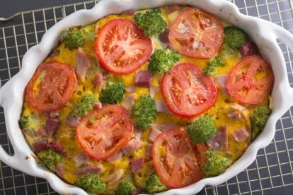 overhead of savory bread pudding in white oval casserole with broccoli and tomato